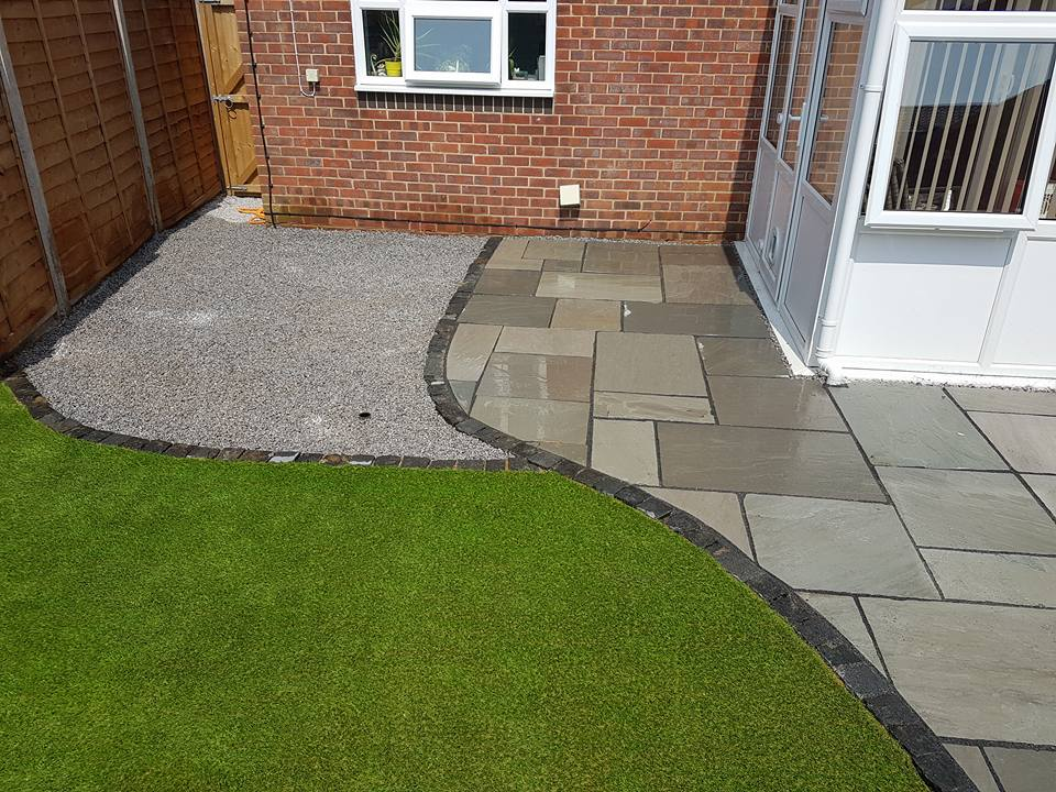 Sandstone paving with granite edging and artificial grass in our Gosport garden design
