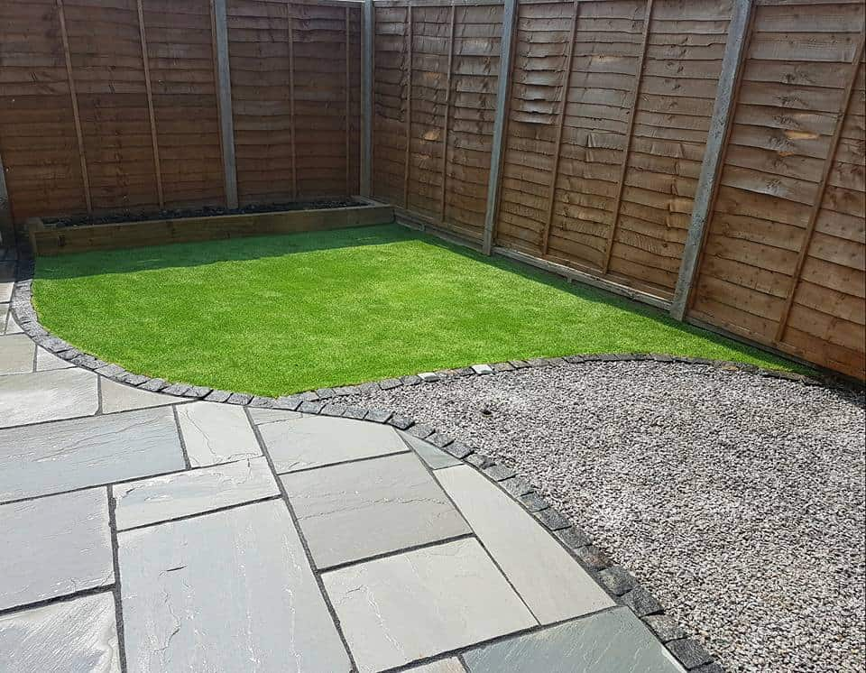 Sandstone paving with granite edging and artificial grass in our Hampshire garden design